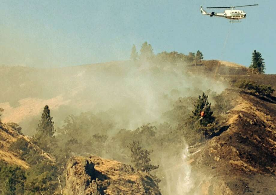 A drop from the bucket: A helicopter dumps water on the Rowena Fire about seven miles west of The Dalles, 