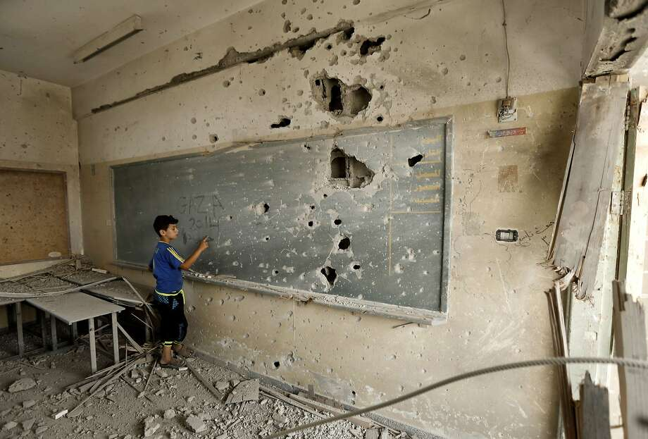 School's out indefinitely: A Palestinian boy writes on a shrapnel-riddled backboard at the heavily damaged Sobhi Abu Karsh 
