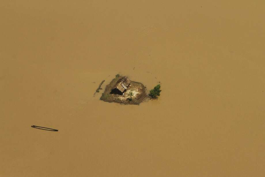 Water, water, everywhere:Monsoon flooding in Kendrapara district, India's Orissa state, turns a house into an island. Photo: Biswaranjan Rout, Associated Press