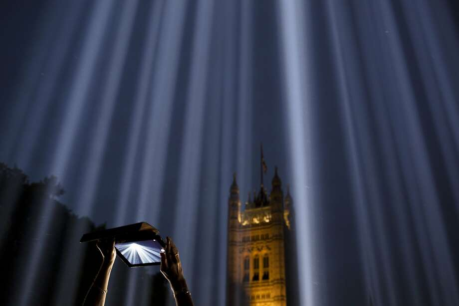 A woman uses a tablet to photograph shafts of light piercing the night sky at the 