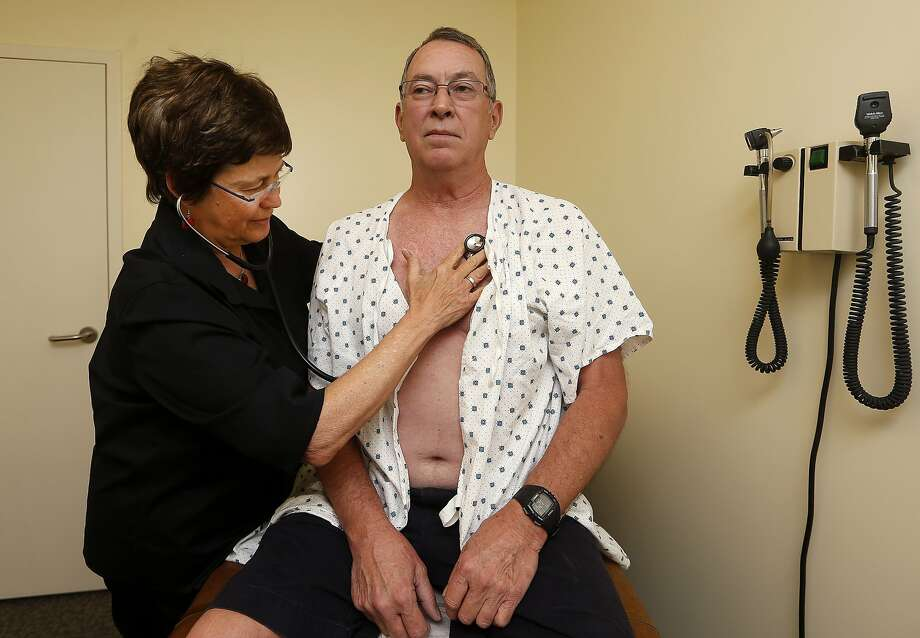 Dr. Melanie Thompson examines HIV patient Brian Albright in her office in Atlanta. Albright, who was diagnosed with HIV in 1987, estimates his prescription drugs cost $30,000 a year. Photo: John Bazemore, Associated Press