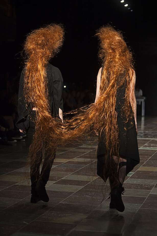 It takes two to tangle: Models share the hair while showing creations by Danish designer Barbara 