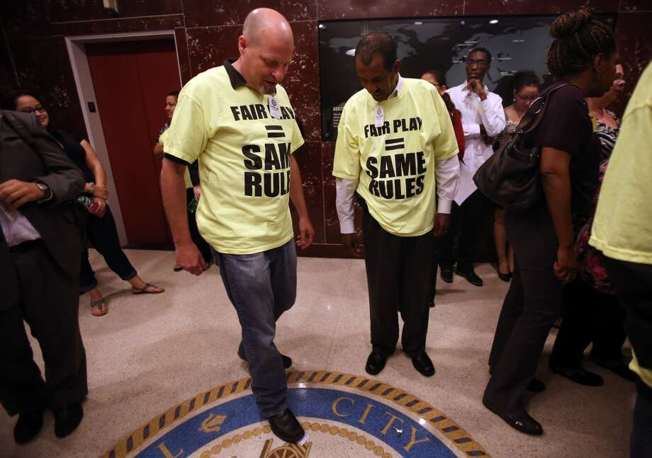 """My Taxi License is worthless now. Anyone could do what I do"" says Clark Darrell who 'throws away' his City of Houston Taxi License by stomping on it as symbolism of his disappointment on the vote by the Houston City Council which will bring regulatory change to allow new entrants like Uber and Lyft to operate legally in city on Wednesday, Aug. 6, 2014, in Houston. ( Mayra Beltran / Houston Chronicle ) Photo: Houston Chronicle"
