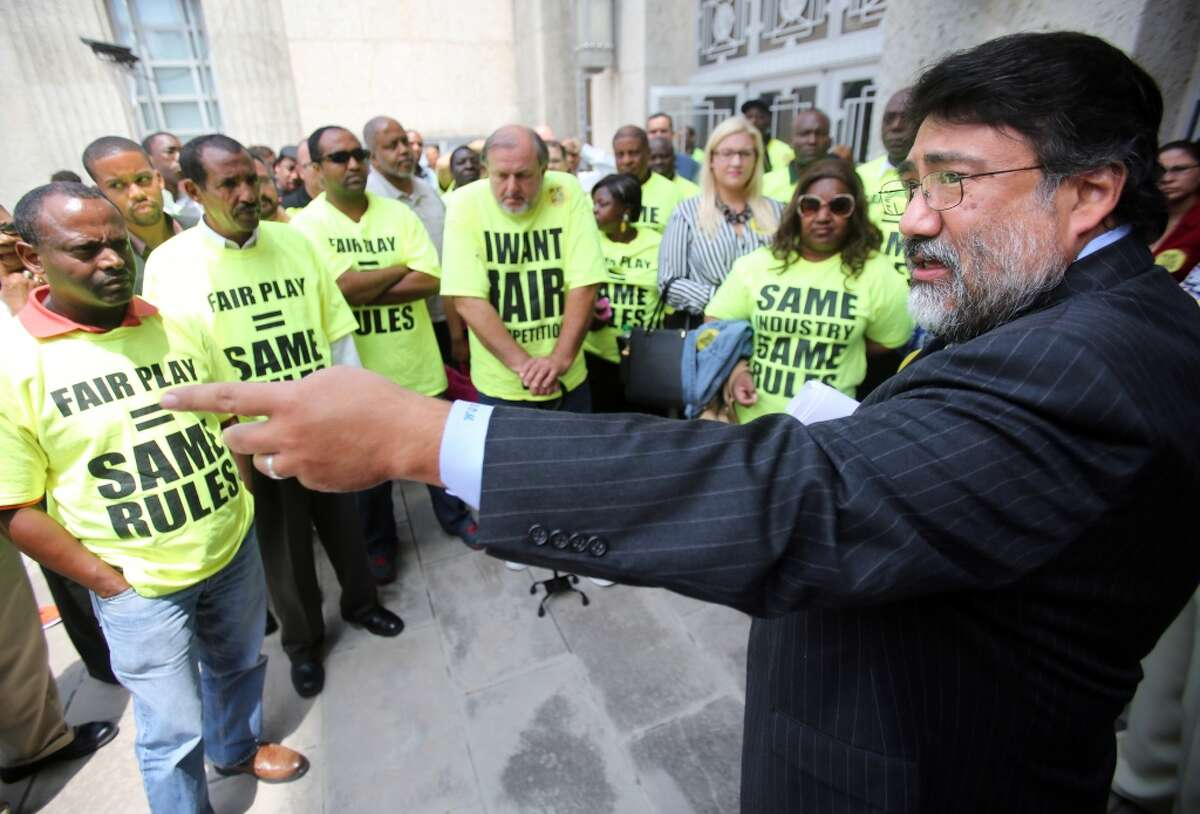 Roman Martinez, CEO of Texas Taxis, rallies outside City Hall with taxi drivers who are disappointed with City Council's vote that will bring regulatory change and allow new entrants like Uber and Lyft to operate legally in the city on Wednesday, Aug. 6, 2014, in Houston. ( Mayra Beltran / Houston Chronicle )