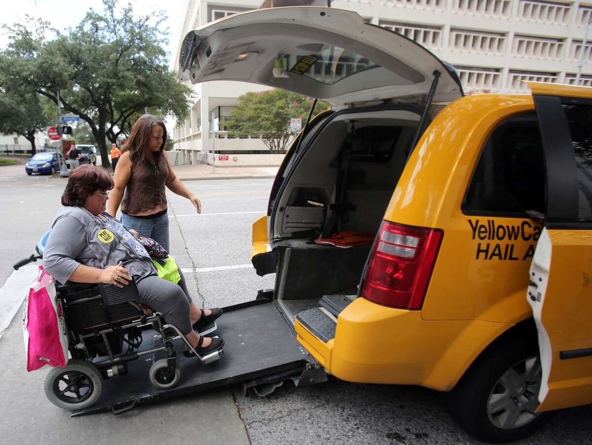 Taxi driver Crystal Gardner helps Lara Posadas board the taxi in front of Houston City Hall after City Council's vote on Aug. 6, 2014, allowing Uber to operate in the city.