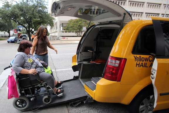 Taxi driver Crystal Gardner helps Lara Posadas board the taxi in front of City Hall after City Council's vote on Wednesday, Aug. 6, 2014, in Houston.  The Taxi industry argues the handicap riders will not benefit from new regulations since Uber and Lyft rides are not wheelchair accessible.   ( Mayra Beltran / Houston Chronicle )