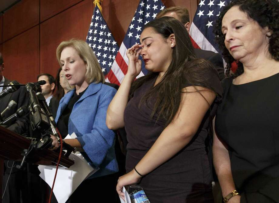 A victim of sexual assault (center) and her mother join Sen. Kirsten Gillibrand, D-N.Y.,  during a news conference in late July to discuss the proposed Campus Accountability and Safety Act. Photo: J. Scott Applewhite / Associated Press / AP