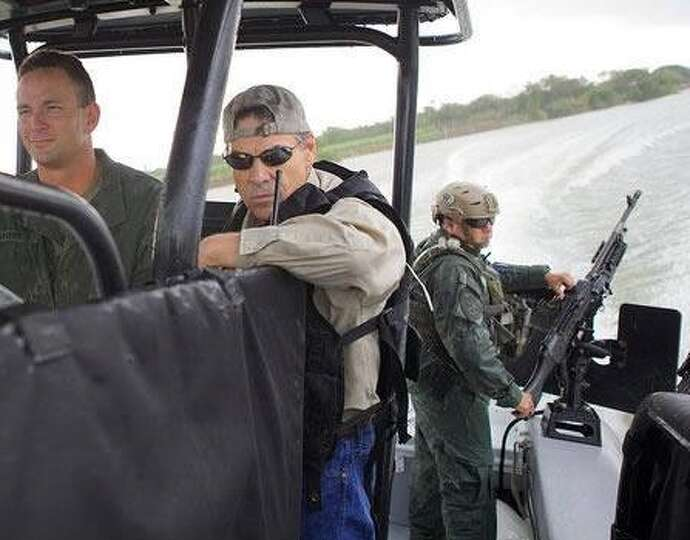 Gov. Rick Perry  poses for a photo op on a Department of Public Safety gun boat during a July 2014 t