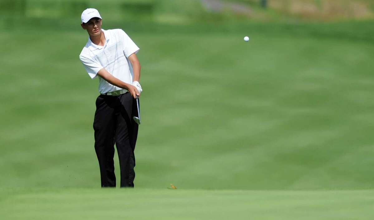 Adam Friedman, of Westport, hits the ball onto the 13th green Wednesday Aug. 6, 2014, during the Borck Memorial Junior Golf Tournament at the Brooklawn Country Club in Fairfield, Conn.