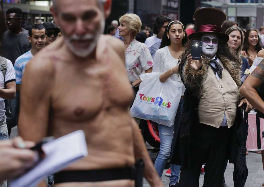"An entertainer dressed as the Penguin character from the comic book series ""Batman"" shoots photos of George Davis who walked through Times Square in the nude after giving a speech. Photo: Julie Jacobson, Associated Press"