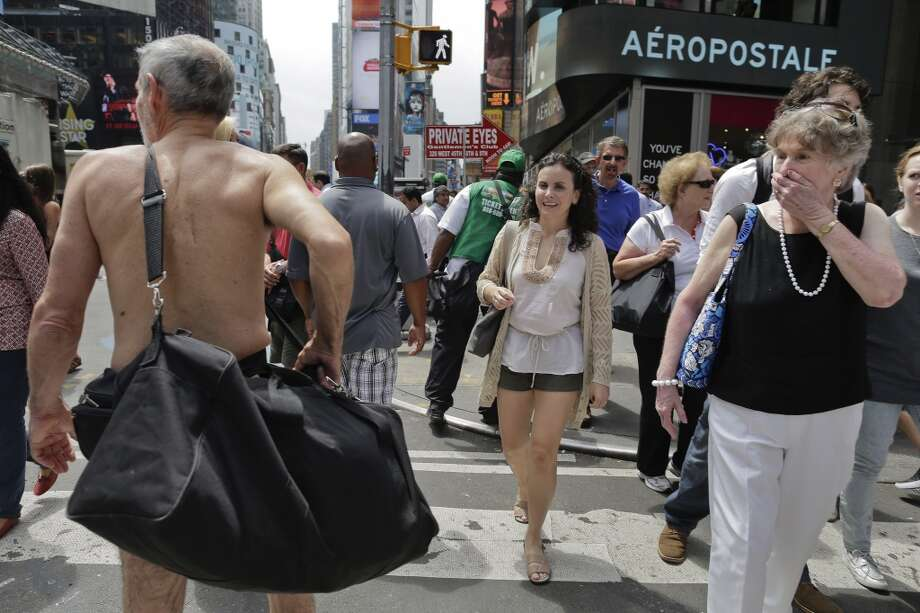 Pedestrians react as George Davis, left, walks nude through Times Square, Wednesday, Aug. 6, 2014, in New York. Photo: Julie Jacobson, Associated Press