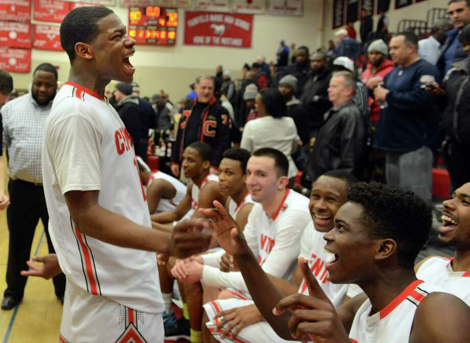 Central's Tyler Ancrum, left, celebrates with teammates following their FCIAC championship win over  Greenwich Thursday, Mar. 6, 2014, at Fairfield Warde High School in Fairfield, Conn. Photo: Autumn Driscoll / Connecticut Post