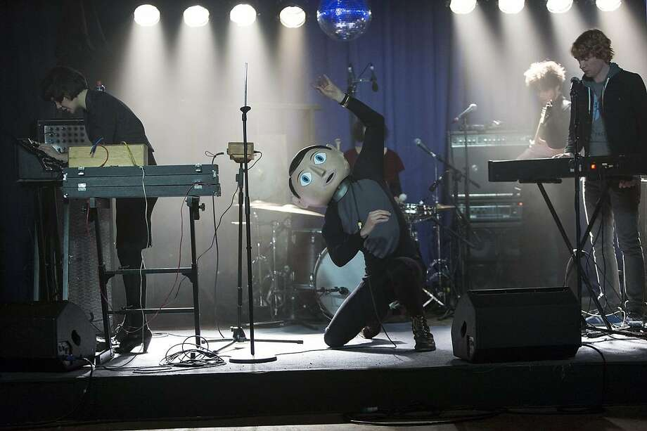 "Claire (Maggie Gyllenhaal), Frank (Michael Fassbender), who is wearing the weird head he never takes off, and Jon (Domnhall Gleeson) perform in their avant-garde band in ""Frank."" Photo: Magnolia Pictures"