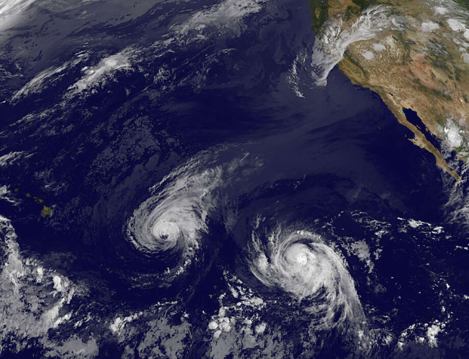 This satellite image taken Wednesday shows Hurricane Iselle, center, and tropical storm Julio, right. Though it's not clear how damaging the storms could be, many in Hawaii aren't taking any chances. Photo: HOPD / NOAA
