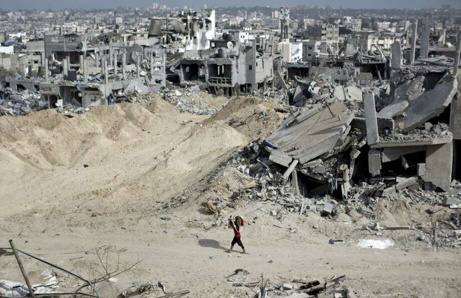 A Palestinian youth salvages items from the rubble in Gaza City's al-Tufah neighborhood as the fragile cease-fire entered a second day on Aug. 6.  Photo: MAHMUD HAMS, Staff / AFP