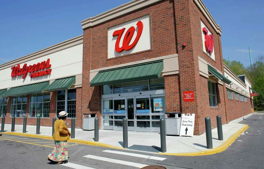In this Wednesday, May 14, 2014 photo, a customer walks toward an entrance to a Walgreens store, in Boston. Walgreen plans to keep its roots firmly planted in the United States, saying Wednesday, Aug. 6, 2014 it will no longer pursue an overseas reorganization that would have trimmed the amount of U.S. taxes it pays. (AP Photo/Steven Senne) Photo: Steven Senne, STF / AP