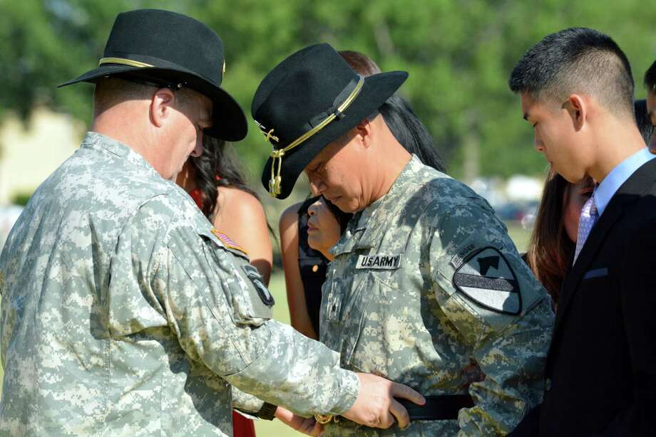 Fort Hood commander, Lt. Gen. Mark Milley adjusts the commanders belt on the waist of Col. Viet Luong during his promotion ceremony, Wednesday, Aug. 6, 2014 as his son Brandon Luong, 17, watches. Luong has become the first Vietnamese-American to reach the rank of general in the U.S. Army. (AP Photo/Killeen Daily Herald, Bryan Correira) Photo: Bryan Correira, MBO / Killeen Daily Herald