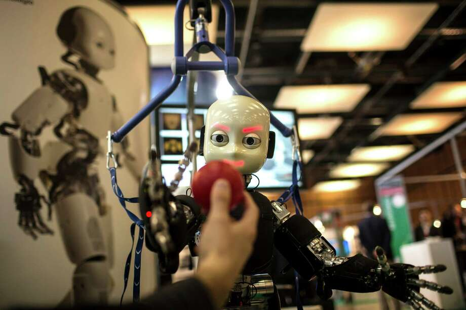 An iCub robot tries to catch a ball during a European robotics event last year. Experts are divided on whether robots will create or kill human jobs. Photo: Laurent Cipriani, STR / AP