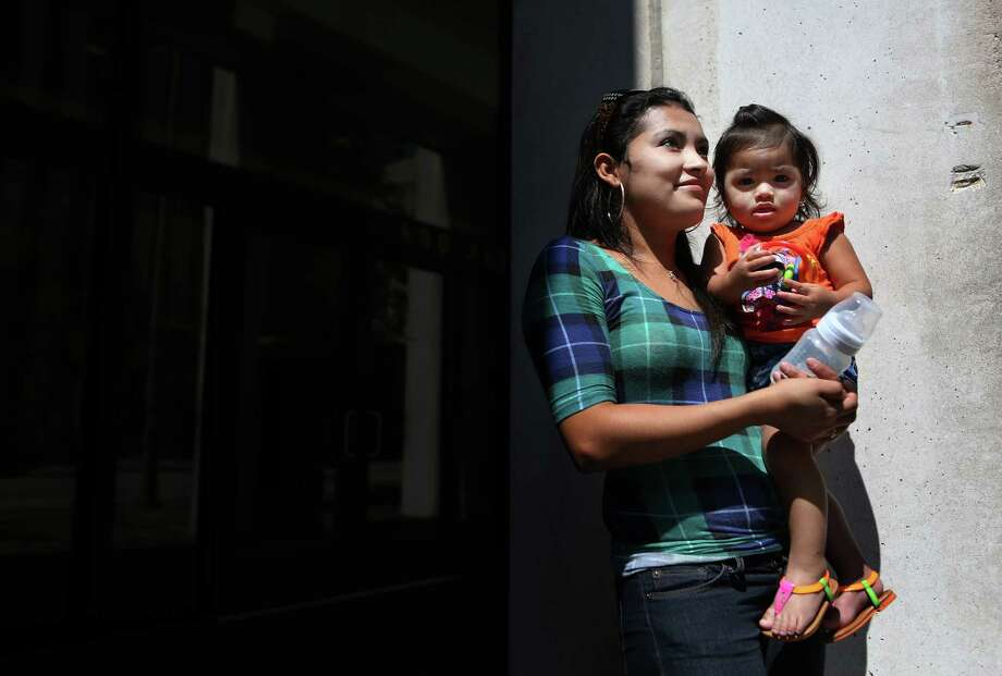 Keydi Vasquez, 21, carries daughter Beancy Cartagena, 1, of Honduras, outside Immigration Court after attending their second hearing since being detained by immigration officials.  Vasquez's hearing has been reset to April 2015. Photo: Mayra Beltran, Houston Chronicle / © 2014 Houston Chronicle