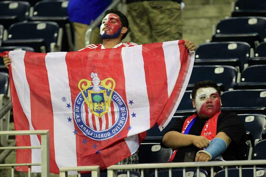 Chivas fan Alejandro Moran holds a flag at Wednesday night's game against AC Milan at NRG Stadium. Photo: Johnny Hanson / Houston Chronicle