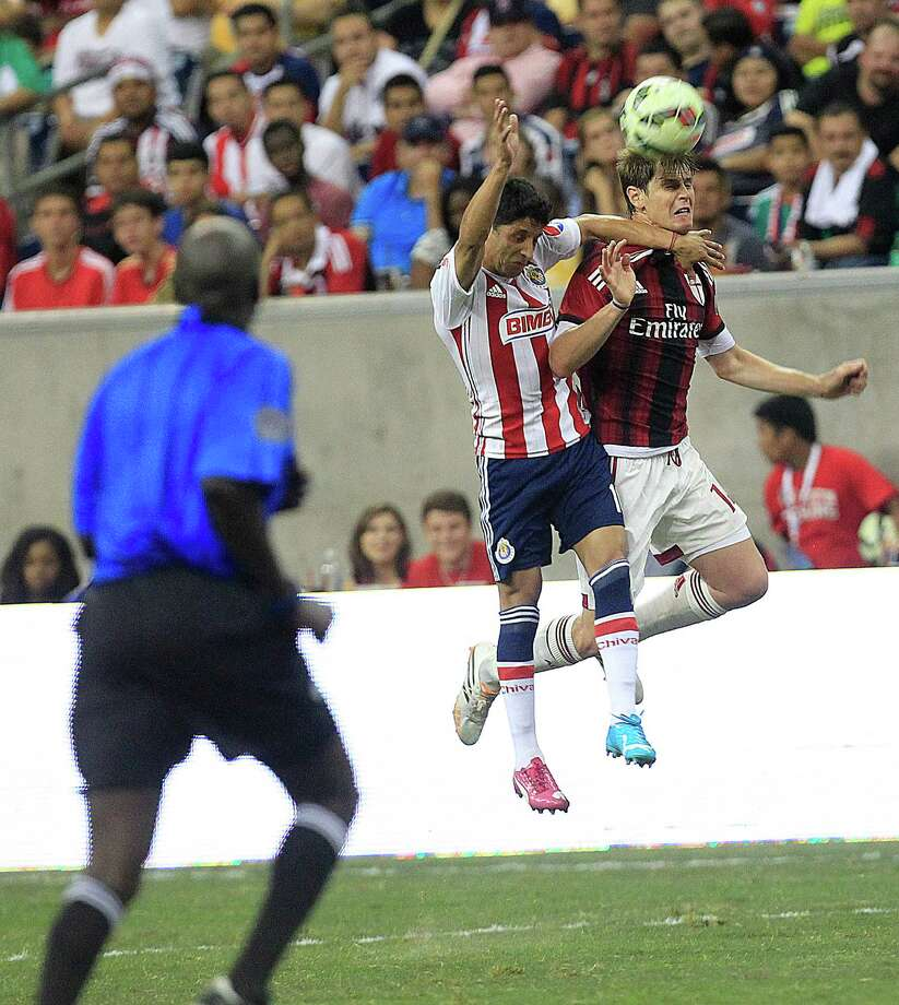 A.C. Milan forward Giampaolo Pazzini (11) and Chivas forward Angel Reyna (10) battle for the ball in the second half as A.C. Milan defeated Chivas de Guadalajara 3-0 in an international friendly soccer game at NRG Stadium Wednesday, Aug. 6, 2014, in Houston. Photo: Johnny Hanson, Houston Chronicle / © 2014  Houston Chronicle