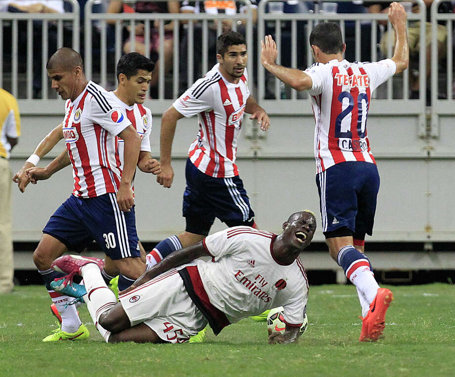 A.C. Milan forward Mario Balotelli (45) goes down surrounded by Chivas players in the first half as A.C. Milan played Chivas de Guadalajara in an international friendly soccer game at NRG Stadium Wednesday, Aug. 6, 2014, in Houston. Photo: Johnny Hanson, Houston Chronicle / © 2014  Houston Chronicle