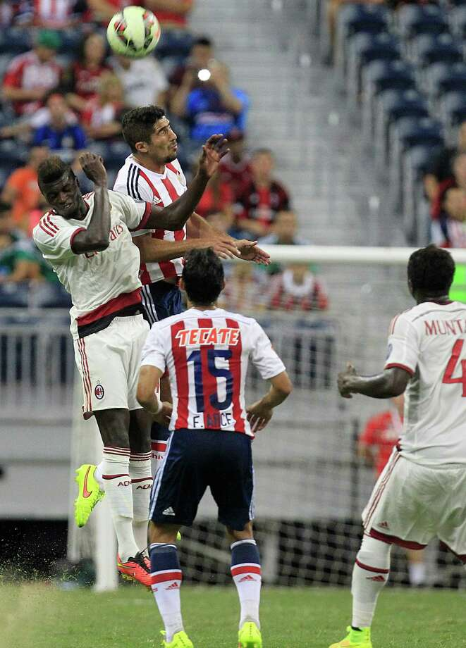A.C. Milan forward Mbaye Niang (19) and defender Jair Pereira (4) battle for the ball as A.C. Milan played Chivas de Guadalajara in an international friendly soccer game at NRG Stadium Wednesday, Aug. 6, 2014, in Houston. Photo: Johnny Hanson, Houston Chronicle / © 2014  Houston Chronicle