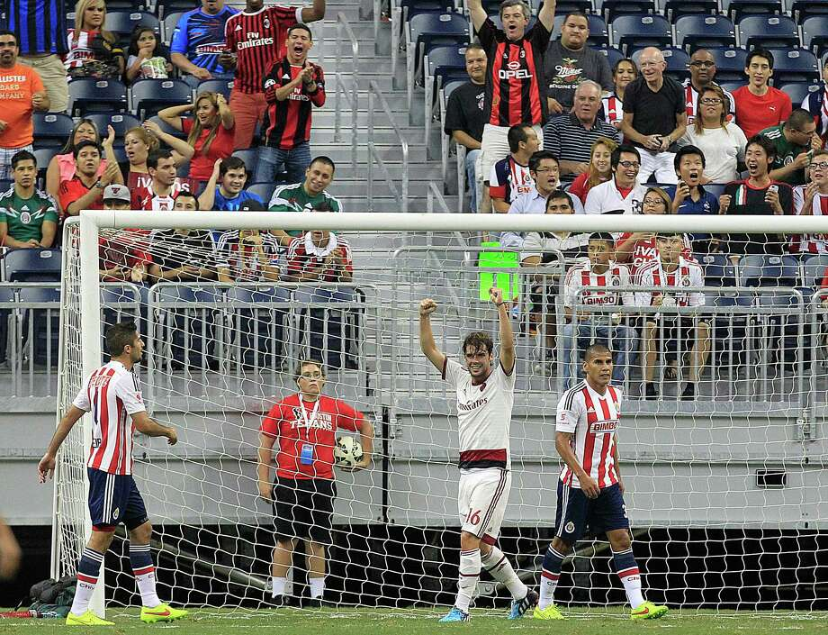 A.C. Milan midfielder Andrea Poli (16) celebrates the first goal scored by A.C. Milan forward Mbaye Niang (19) as A.C. Milan played Chivas de Guadalajara in an international friendly soccer game at NRG Stadium Wednesday, Aug. 6, 2014, in Houston. Photo: Johnny Hanson, Houston Chronicle / © 2014  Houston Chronicle