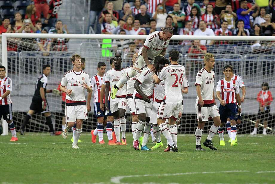 A.C. Milan defender Philippe Mexes (5) jumps on the back of A.C. Milan forward Mario Balotelli (45) after Balotelli scored the second goal in the first half as A.C. Milan played Chivas de Guadalajara in an international friendly soccer game at NRG Stadium Wednesday, Aug. 6, 2014, in Houston. Photo: Johnny Hanson, Houston Chronicle / © 2014  Houston Chronicle