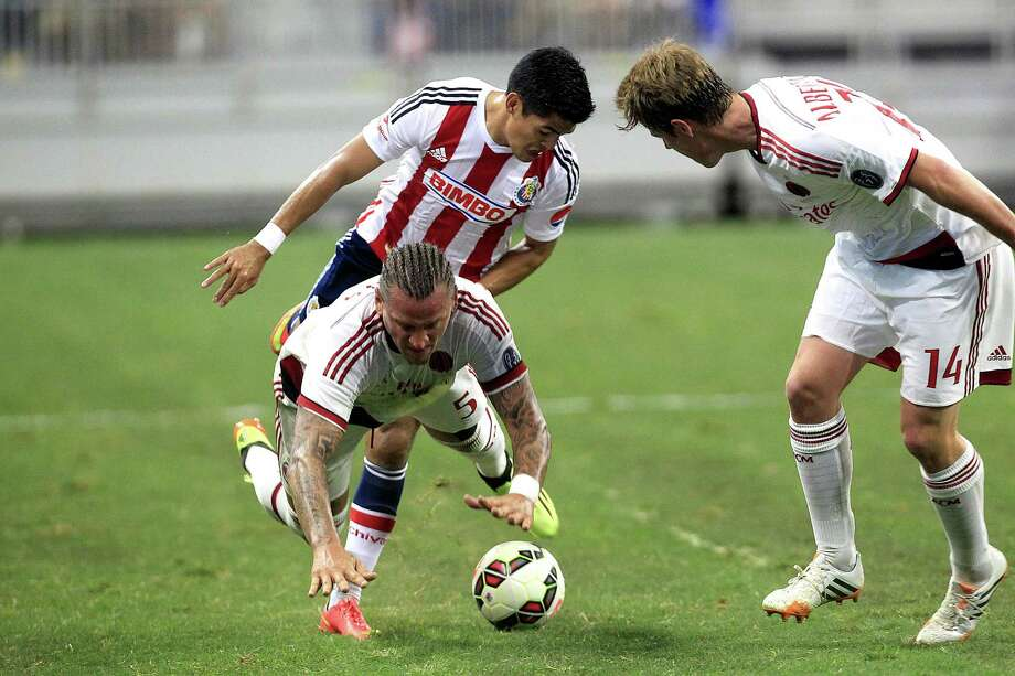 Chivas forward Aldo De Nigris (11) gets tangled up with A.C. Milan defender Philippe Mexes (5) as A.C. Milan defender Michaelangelo Albertazzi (14) looks on as A.C. Milan played Chivas de Guadalajara in an international friendly soccer game at NRG Stadium Wednesday, Aug. 6, 2014, in Houston. Photo: Johnny Hanson, Houston Chronicle / © 2014  Houston Chronicle