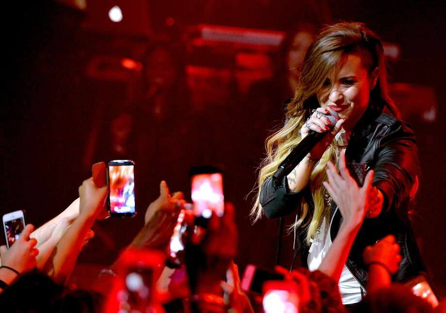 This file image of a concert with with singer Demi Lovato demonstrates the prevalence of cell phones at performances. A new Apple patent could prevent users from recording in places where it's not allowed. Photo: Kevin Winter, Getty Images