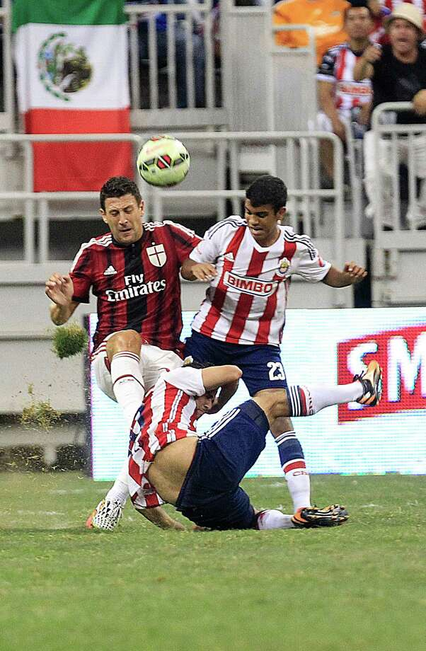 A.C. Milan defender Daniele Bonera (25) and Chivas forward Alberto Garcia (23) and midfielder Sergio Napoles (13) battle for the ball in the second half as A.C. Milan defeated Chivas de Guadalajara 3-0 in an international friendly soccer game at NRG Stadium Wednesday, Aug. 6, 2014, in Houston. Photo: Johnny Hanson, Houston Chronicle / © 2014  Houston Chronicle