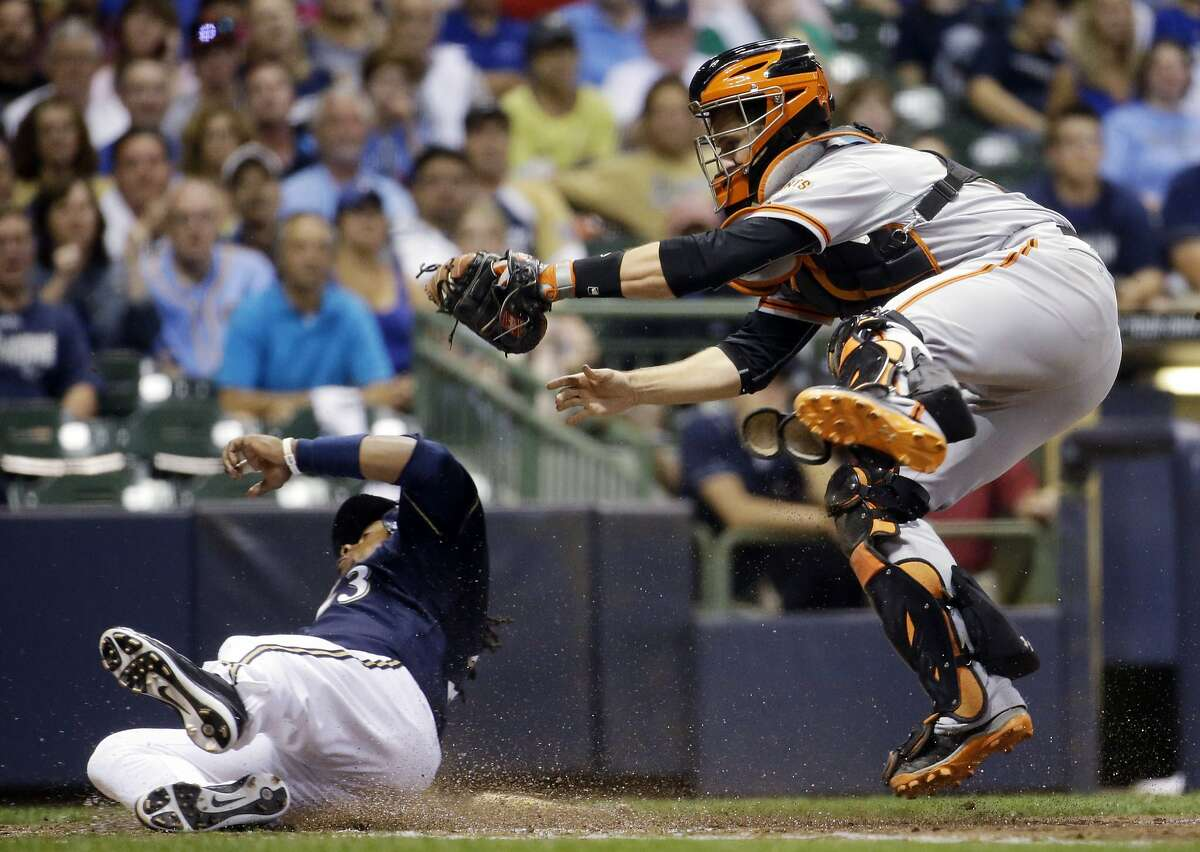 Giants catcher Buster Posey hangs on to the ball after tagging the Brewers' Rickie Weeks during the seventh inning.