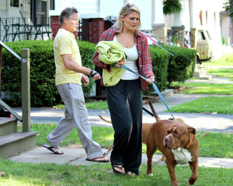 Kevin and Lindsay McKearn walk their pet dogs to the animal control van to be taken away Thursday morning, Aug. 7, 2014, in Schenectady N.Y. (Selby Smith/Special to the Times Union) Photo: Selby Smith / 00028075A