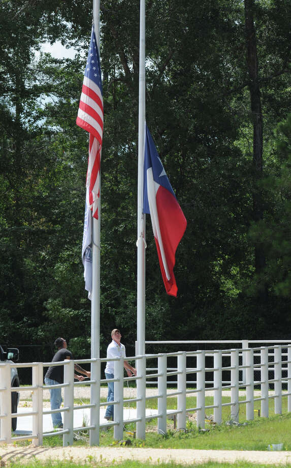 Two men lower flags to half staff at a Village Mills business after an electrical accident killed three employees on Wednesday. Photo taken Guiseppe Barranco/@spotnewsshooter Photo: Guiseppe Barranco, Photo Editor