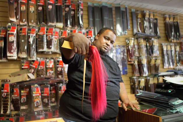 Don Hilliard holds a hair extension after burglars broke into Brashae's Beauty Supply, Thursday, Aug. 7, 2014, in Houston. Brashae's is the fourth beauty supply store to get burglarized in eight days. Two men, wearing bandanas and hats, busted the lock of the neighboring business, cut a hole in the wall and pulled out the drywall and insulation before crawling into the beauty supply store. Photo: Cody Duty, Houston Chronicle / © 2014 Houston Chronicle