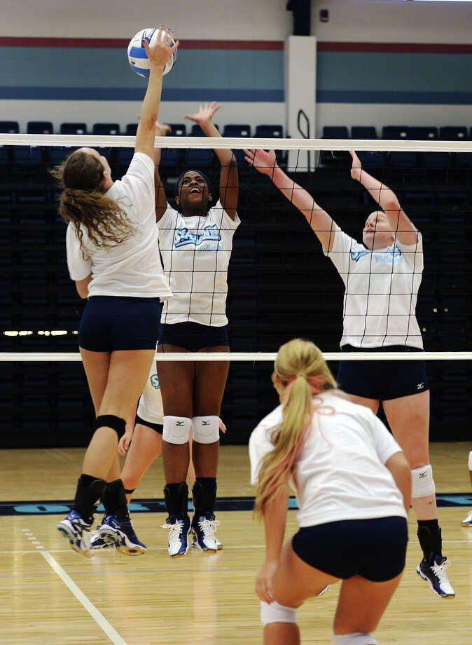 Alana Ailles, left, goes for a shot as Me'Shell Shears, center, and Kristina Merka move to block during practice Wednesday. The Lamar State College-Port Arthur volleyball team hosted a media day at the Carl A. Parker Multipurpose Center on Wednesday afternoon. Photo taken Wednesday 8/6/14 Jake Daniels/@JakeD_in_SETX Photo: Jake Daniels / ©2014 The Beaumont Enterprise/Jake Daniels