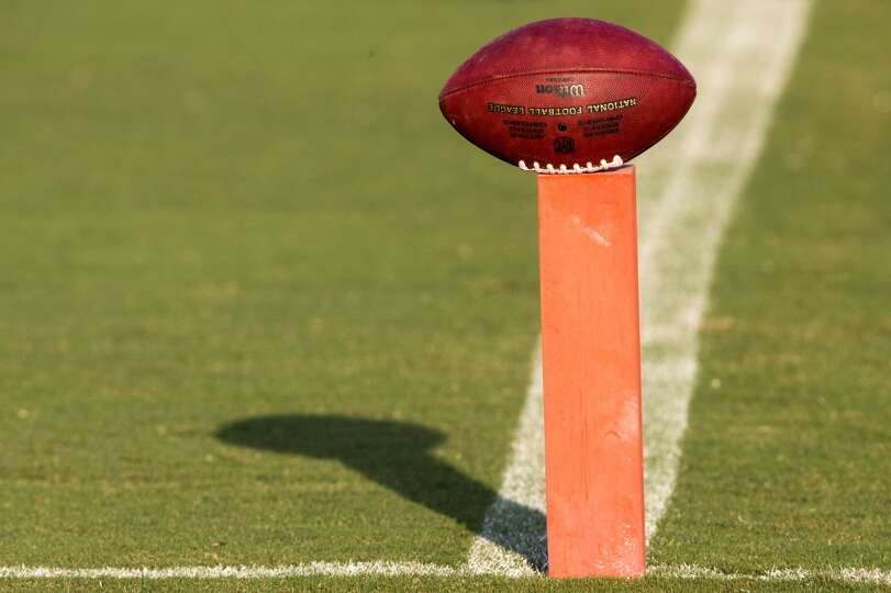 An NFL football sits perched atop an end zone pylon.