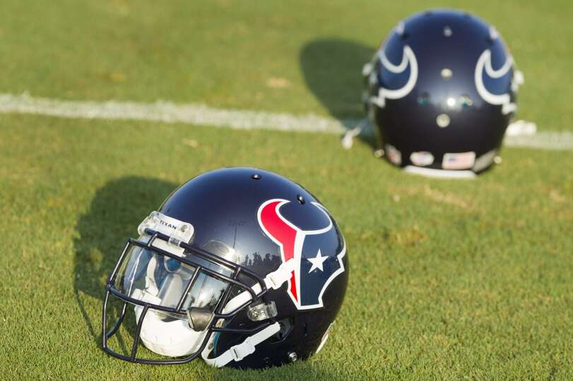A pair of Texans helmets sit on the practice field.