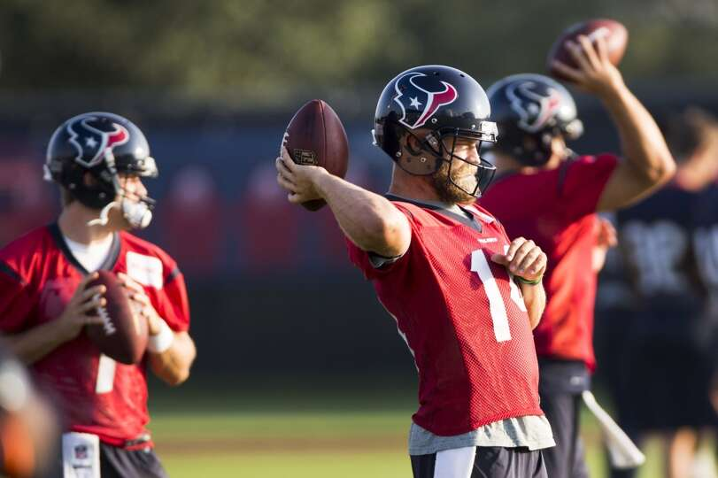 Texans quarterback Ryan Fitzpatrick (14) throws a pass with quarterbacks Case Keenum, left, and Tom