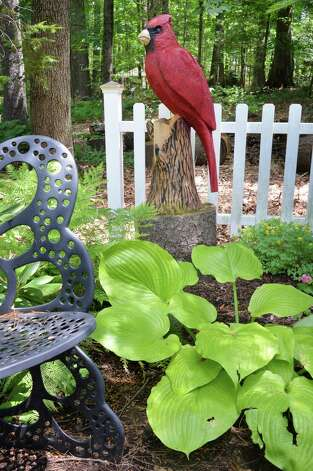 A large carved cardinal by Bryan Ruth above a Hosta plant in Tony and Judy Eastwood's backyard garden Wednesday July 2, 2014, at their home in Saratoga Springs, NY.  (John Carl D'Annibale / Times Union) Photo: John Carl D'Annibale / 00027577A