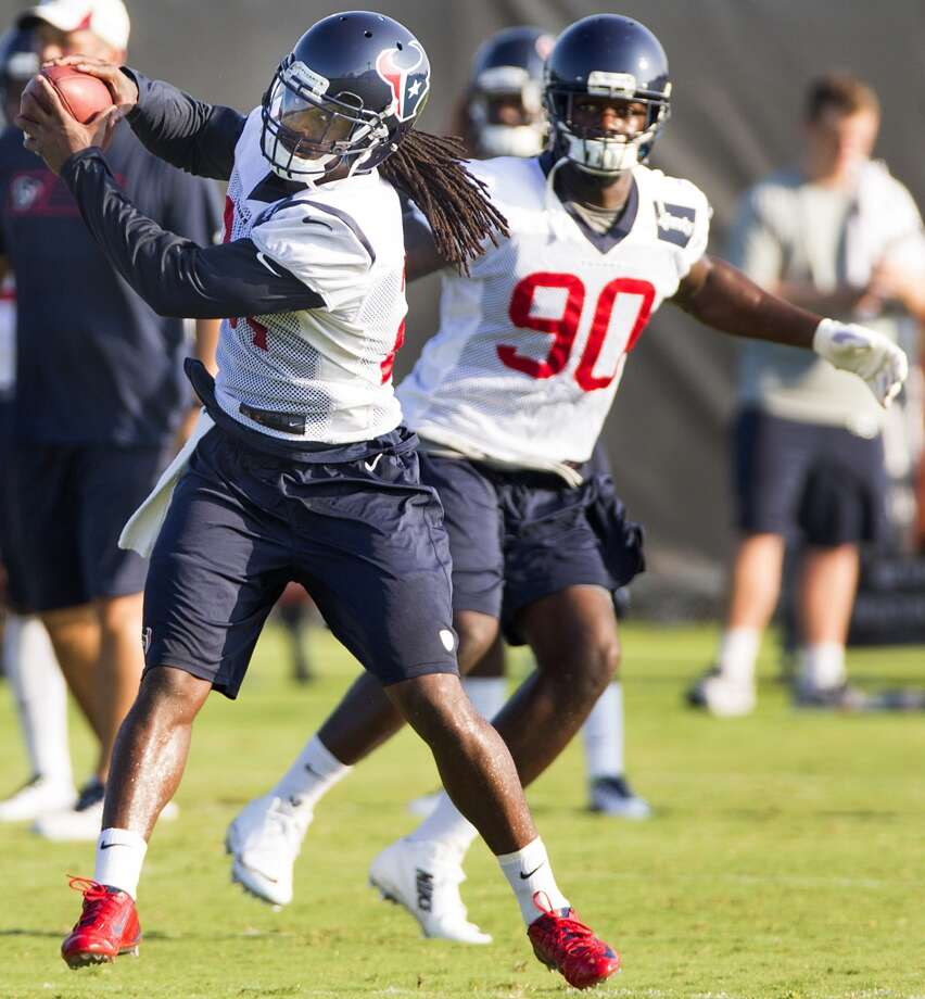 Texans free safety Kendrick Lewis (21) reaches back to catch a football with linebacker Jadeveon Clowney (90) looking on. Photo: Brett Coomer, Houston Chronicle