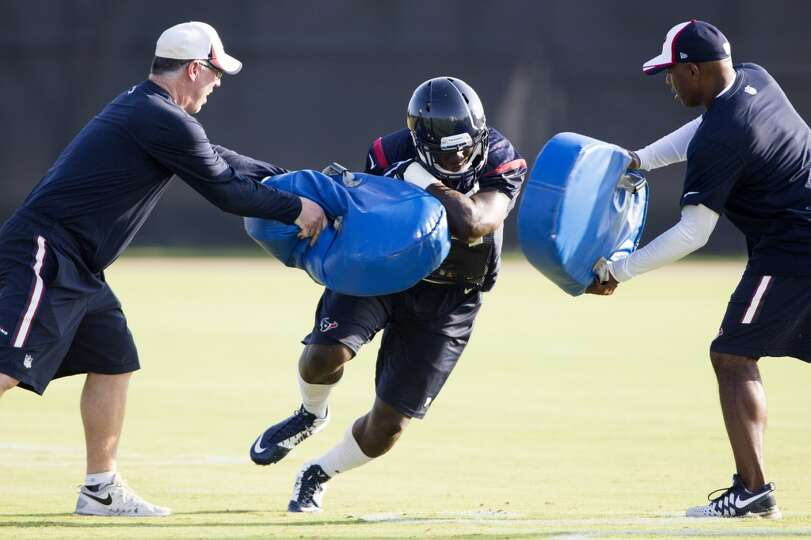 Texans running back Alfred Blue, center, runs with the football after making a catch.