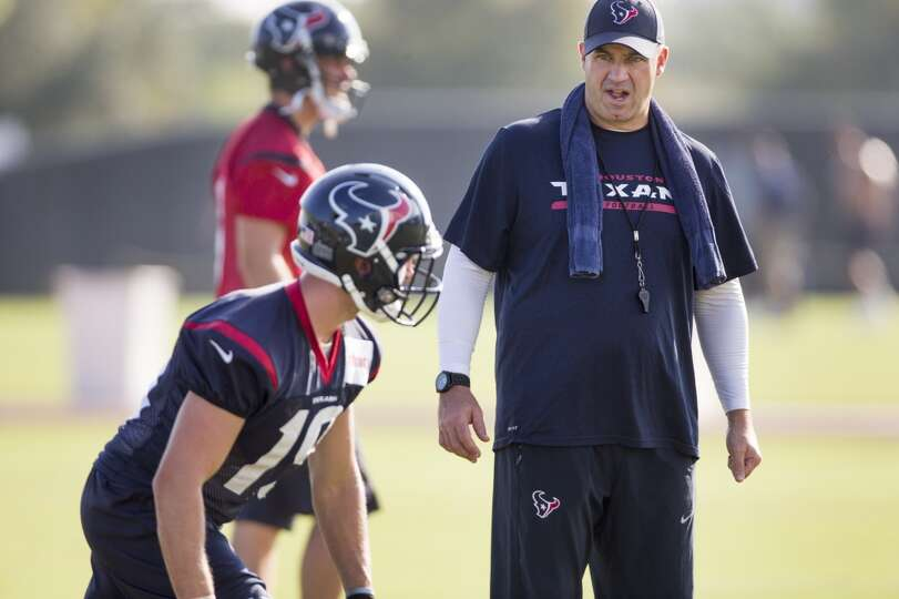 Texans head coach Bill O'Brien works with wide receiver Travis Labhart (19).