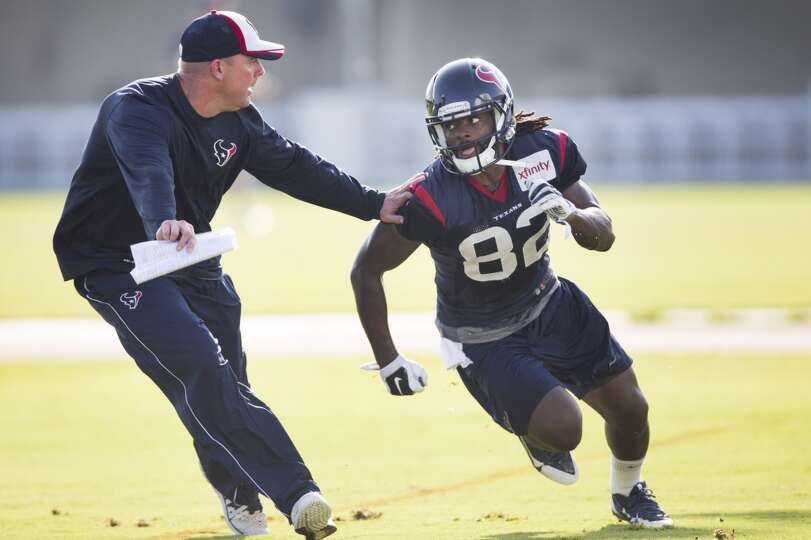 Texans quarterbacks coach George Godsey, left, covers wide receiver Keshawn Martin (82) on a pass ro