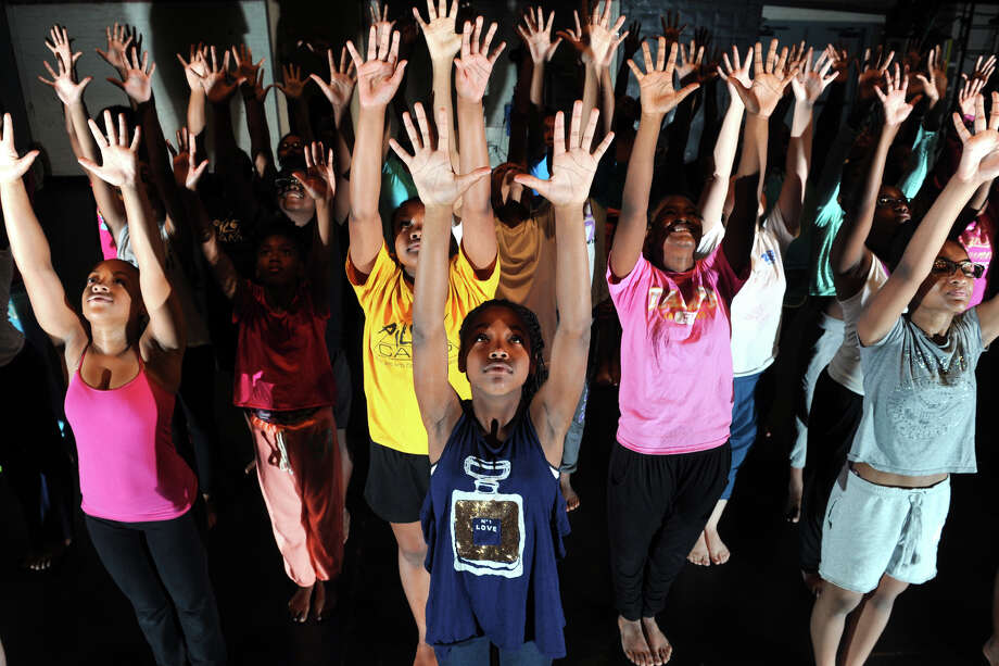 Kalissa Samuel, front and center, rehearses a dance routine with other teens in the summer dance camp run by Neighborhood Studios of Fairfield County, at the Klein Memorial Auditorium, in Bridgeport, Conn. Aug. 7, 2014. Photo: Ned Gerard / Connecticut Post