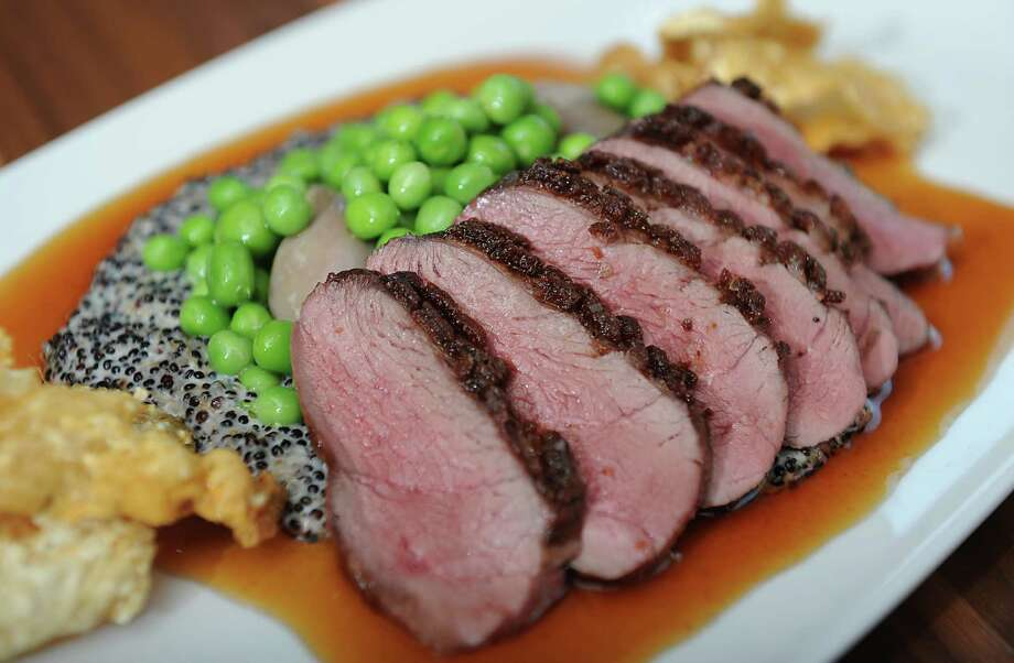 Moulard duck breast at Mingle on the Avenue on Wednesday, July 30, 2014 in Saratoga Springs, N.Y. Confit of leg, creamy organic black quinoa, english peas, jalape–o gastrique, cracklings. (Lori Van Buren / Times Union) Photo: Lori Van Buren / 0027978A