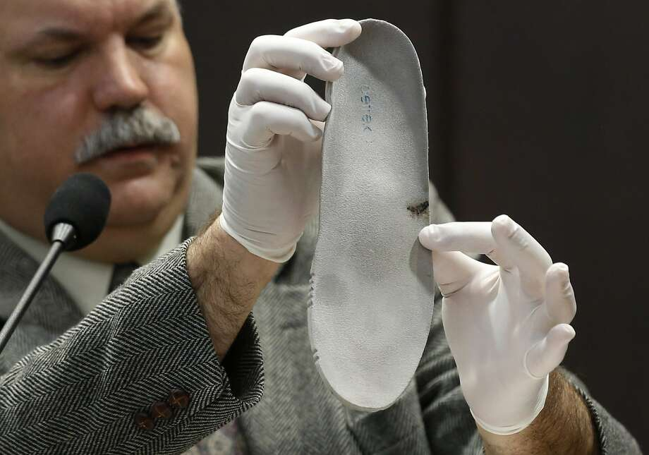 Bloodstained insole: Gainesville (Fla.) Police Crime Scene Investigator Mark Trahan points to blood on a shoe insert 