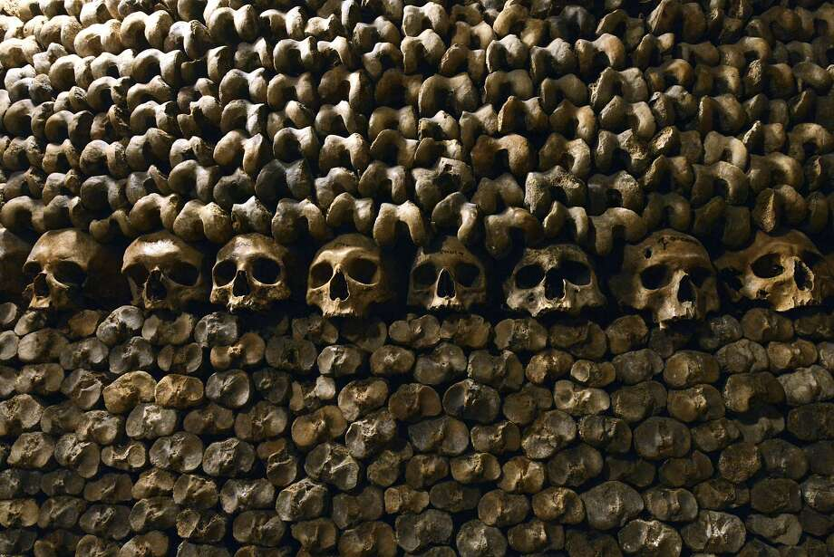 A stack of skulls and bones of long-gone Parisians await visitors in the Catacombs of Paris. These 