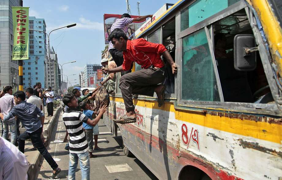 Out the window:Bangladeshi passengers exit a bus in haste after the vehicle was attacked during clashes 